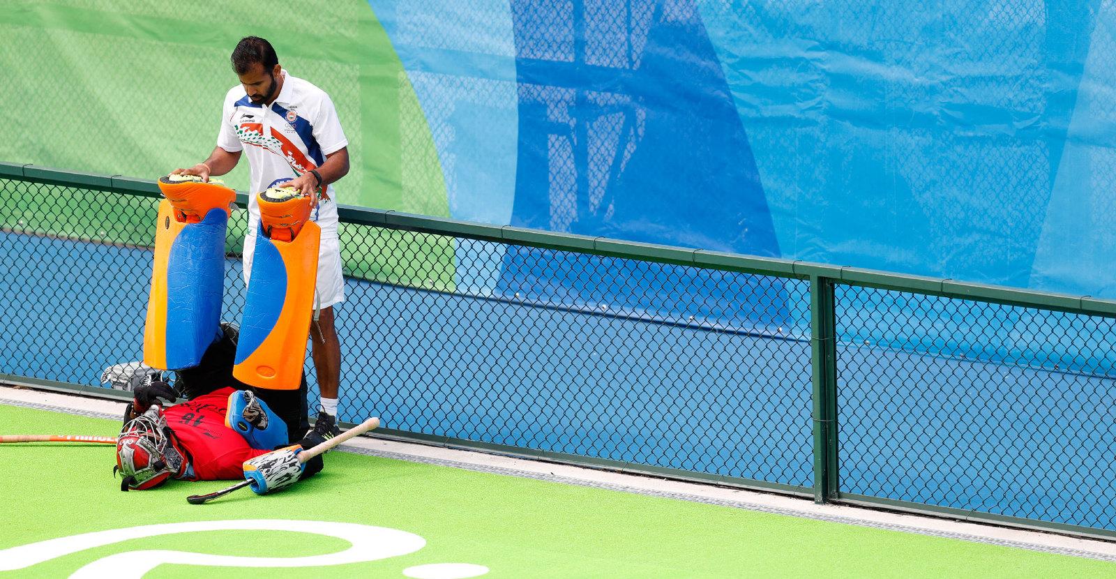Голкиперу хоккейной команды помогают растянуться перед матчем