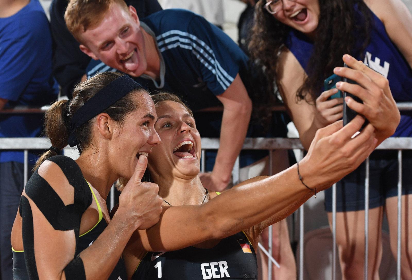Пляжные волейболистки из Германии делают селфи с болельщиками после победного матча