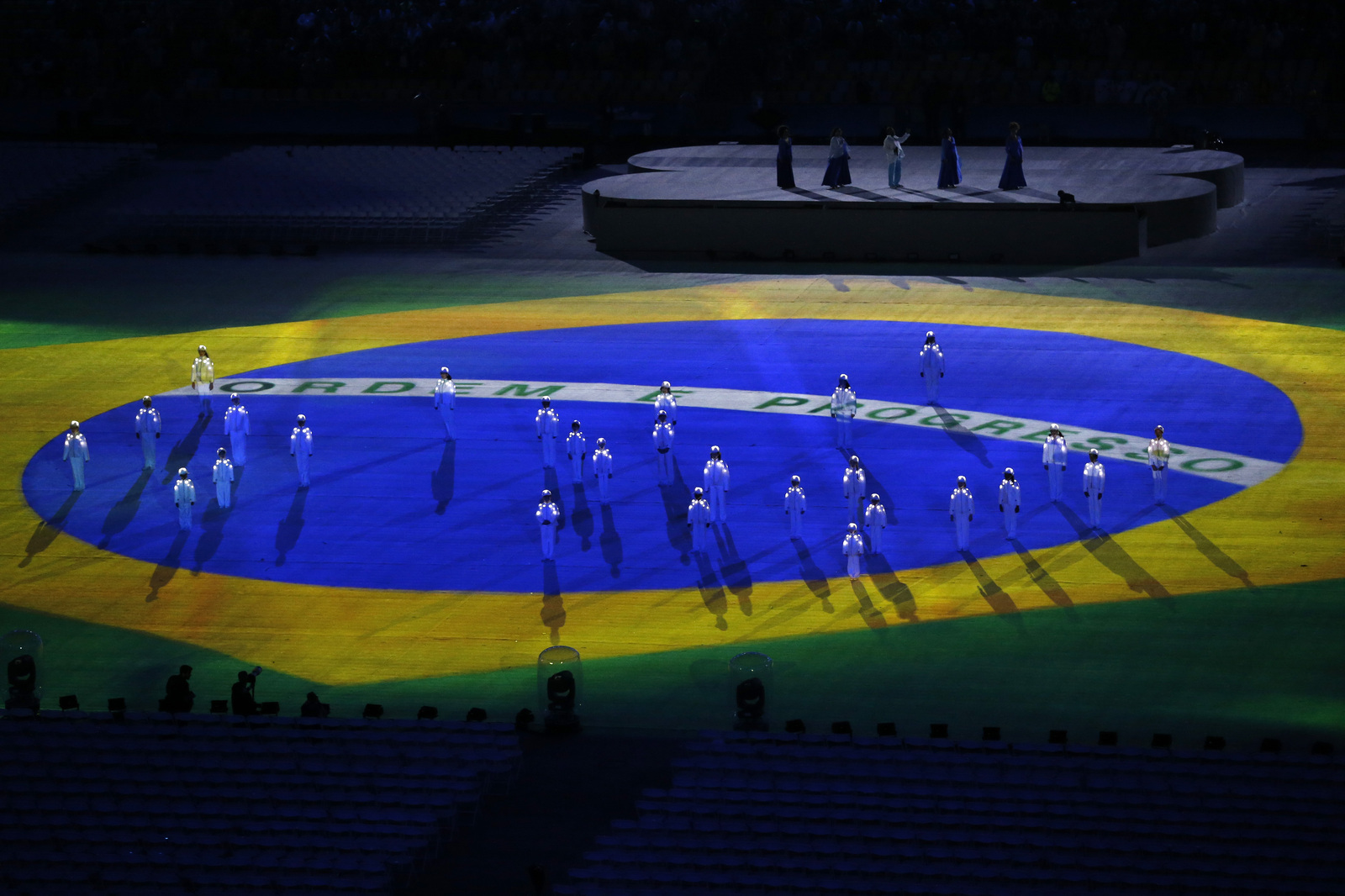 Хор мальчиков поет гимн Бразилии на фоне национального флага