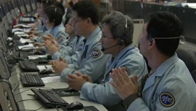 Члены команды управления космическим полётом ещё не верят в свой успех, но уже аплодируют друг другу
