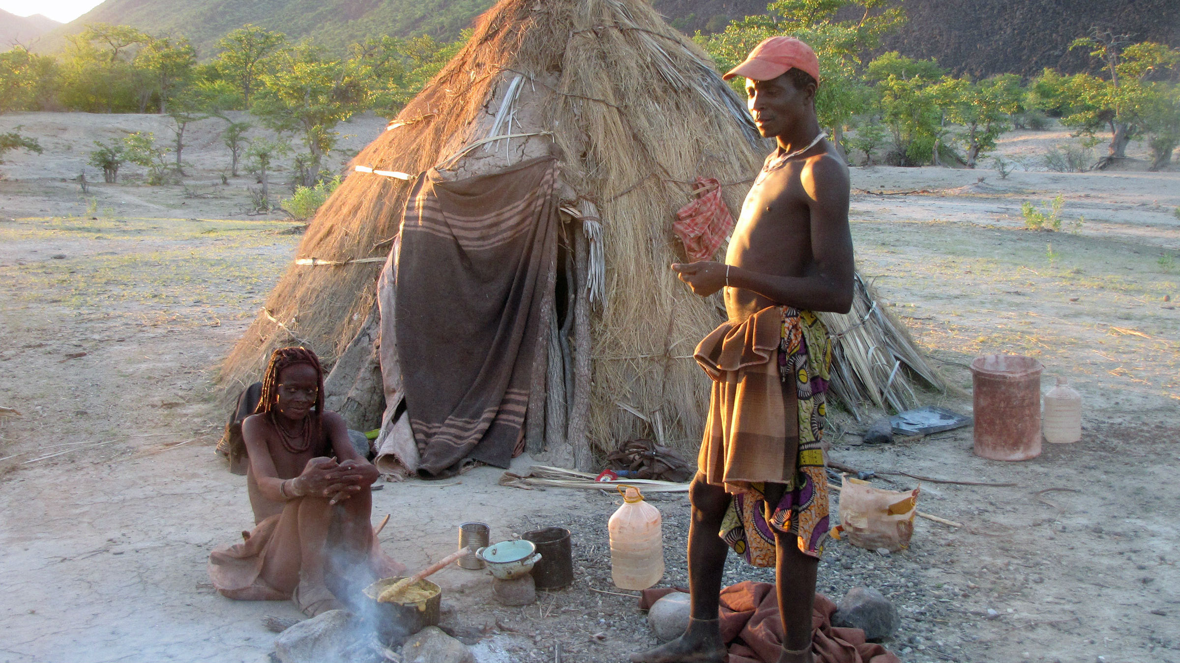 Пара из племени твэй в Намибии вне своего дома