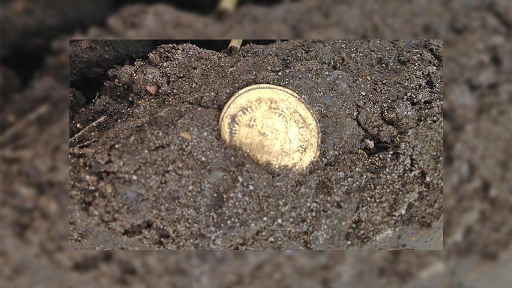Золотой кулон VI века в момент находки. Фото: Godfrey Pratt / BBC