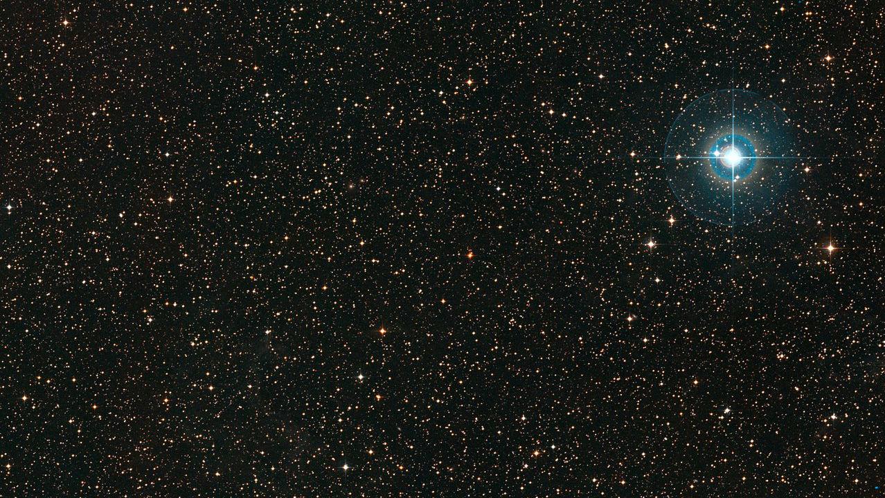 Цветной снимок показывает участок неба вокруг слабой оранжевой карликовой звезды PDS 70 (в центре поля). Яркая голубая звезда справа - χ Centauri.