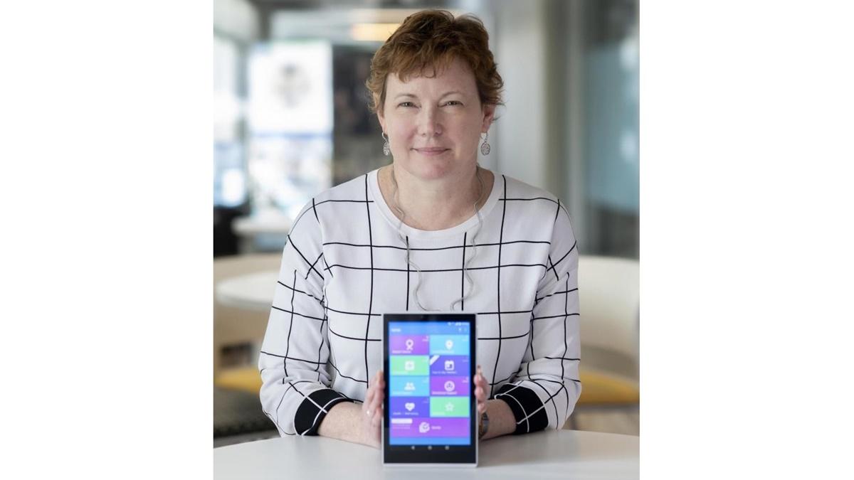 Глава научной группы Элизабет Минатт демонстрирует приложение на планшете.