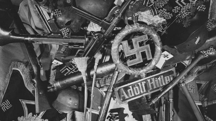 Хроника, 1945 год. Груда немецких символов и оружия -советские трофеи. Автор Марк Редькин.