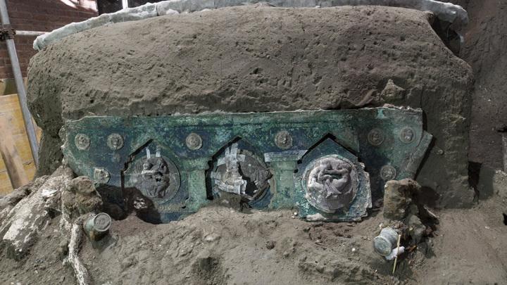 Задняя часть колесницы украшена медальонами с рельефными фигурами.